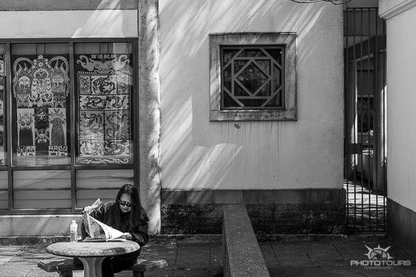 Photo Tours Vancouver black & white image of a woman reading paper in Dr Sun Yat Sen Gardens by Aura McKay