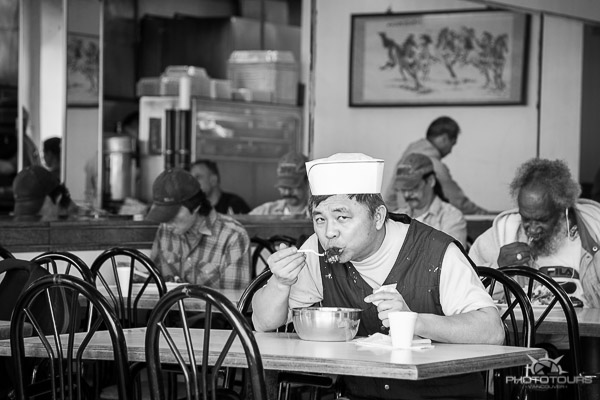 Photo Tours Vancouver man eating noodles with white hat in Chinatown by Aura McKay