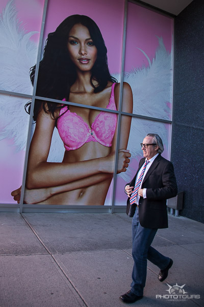 Street photography of man in suit and pink tie in front of Victoria Secret window by Aura McKay