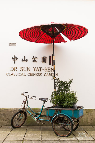 Photo Tours Vancouver entrance to Dr. Sun Yat-Sen gardens with bicylce and red umbrella by Aura McKay